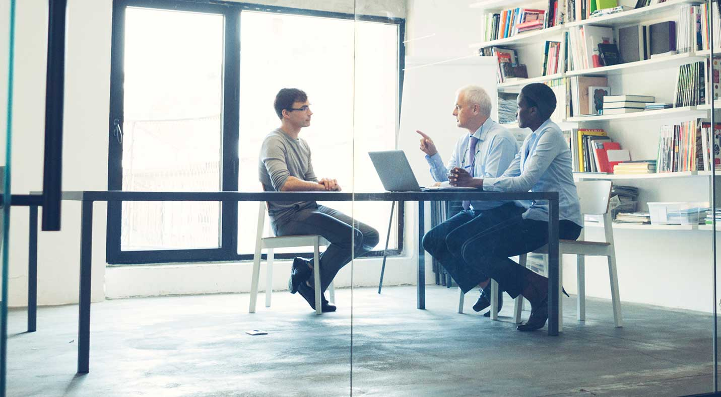 Image of people in a meeting and interviewing a candidate at a conference table.
